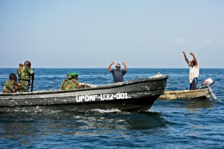 Deux pêcheurs de RDC accusés de pêche illégale se rendent aux militaires ougandais le 13 août 2018 sur le lac Edouard (Photo ISAAC KASAMANI. AFP)