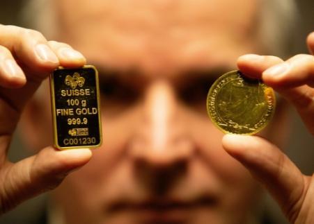 Seamus Fahy, co-fondateur de Merrion Vaults, montre un lingotin suisse et une pièce d'or Britannia, à Dublin le 7 janvier 2019 (Photo PAUL FAITH. AFP)